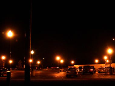 Parking lot with post lamps with arorn globes and HPS lights.